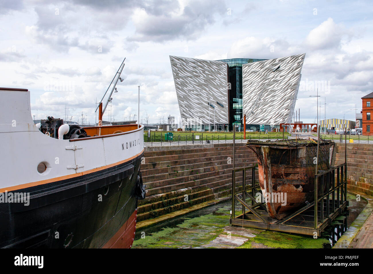 SS Nomadic, the last remaining ship of the White Star Line and the Titanic Belfast museum in the Titanic Quarter of Belfast, Northern Ireland. - Stock Image