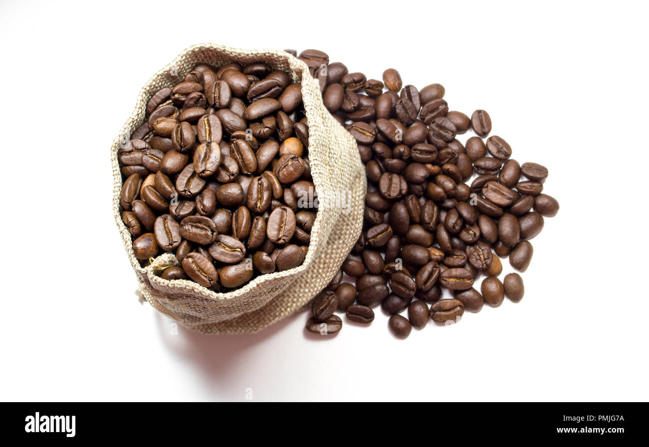 Top view of a full burlap sack overflowing with roasted coffee beans in white background surface. Flat lay. - Stock Image