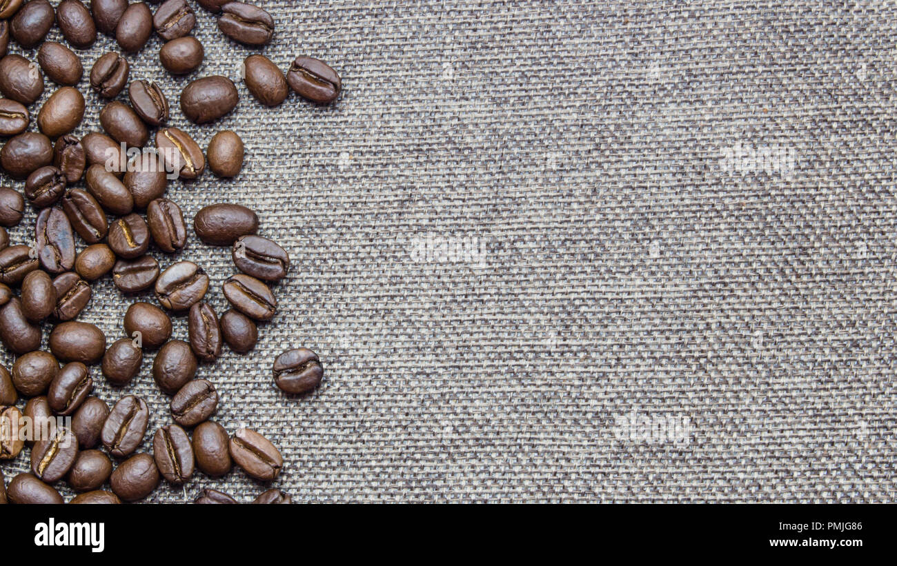 Roasted coffee beans spread around burlap texture background. With available copy space. - Stock Image