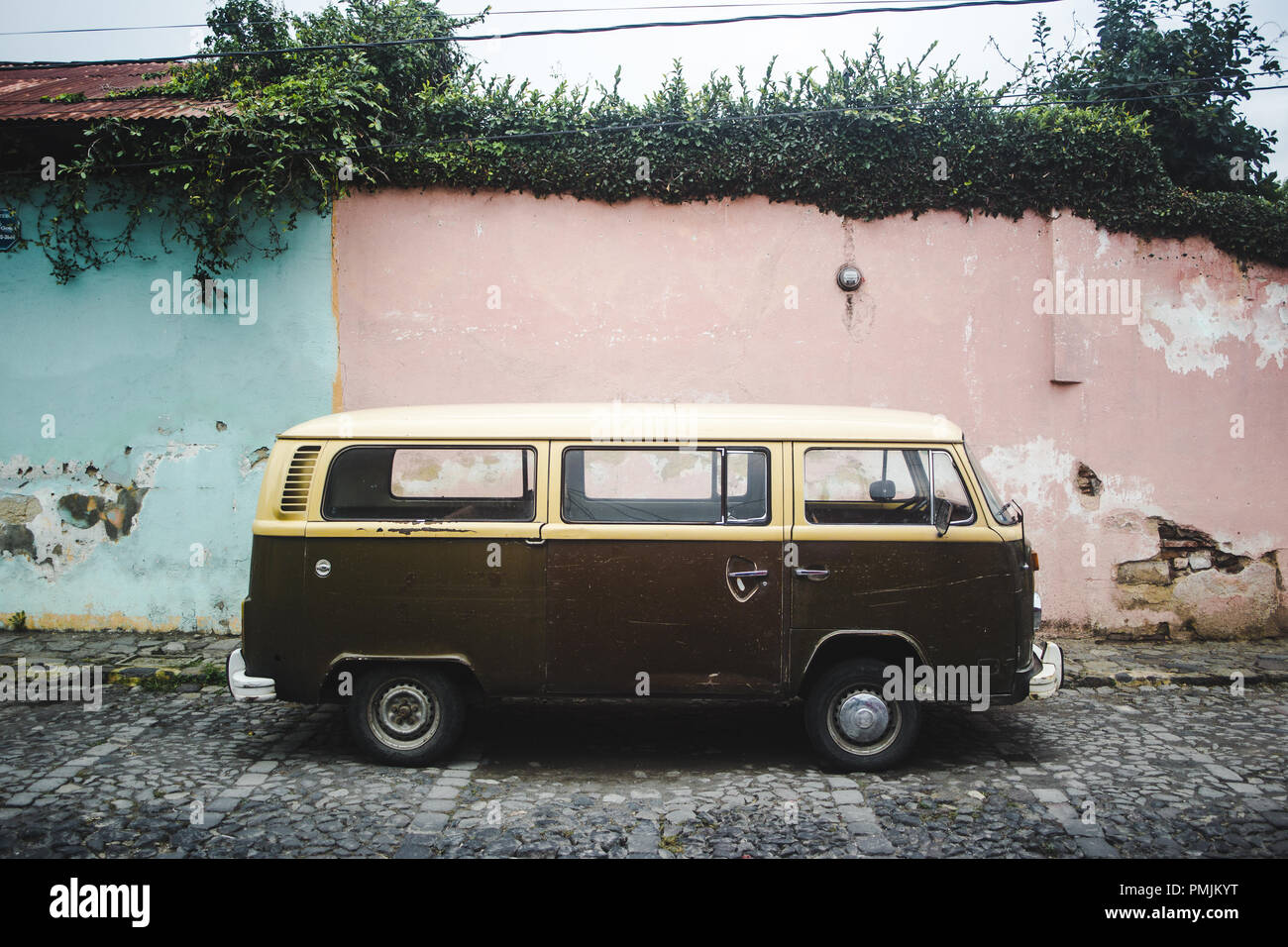 Brown and cream retro campervan from the 1970s parked along a cobbled street with pastel pink and blue walls - Stock Image