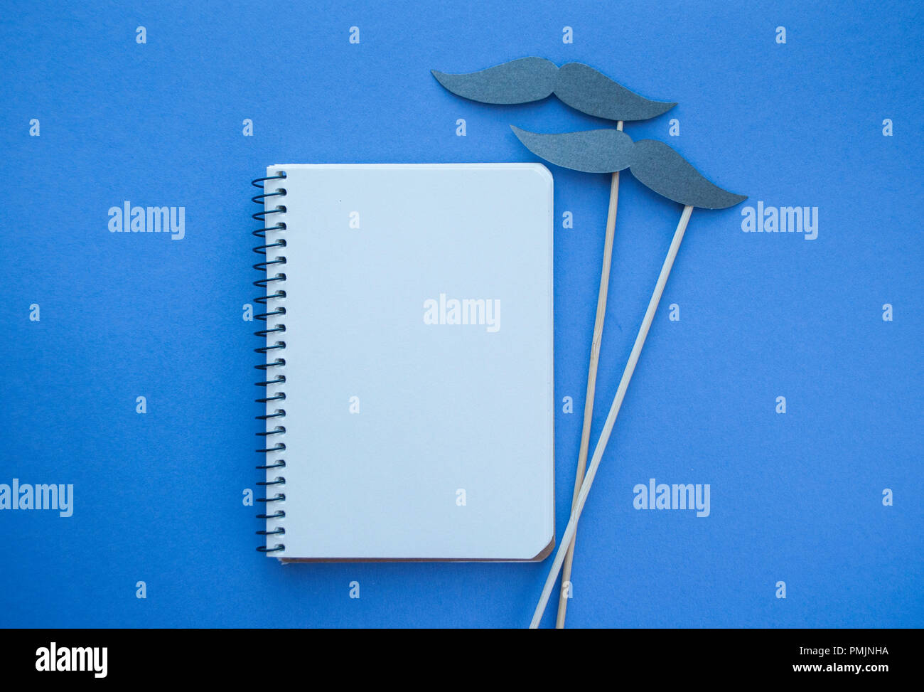 Photo booth props and white notebook on purple background with copyspace. Movember men's health awareness concept. - Stock Image