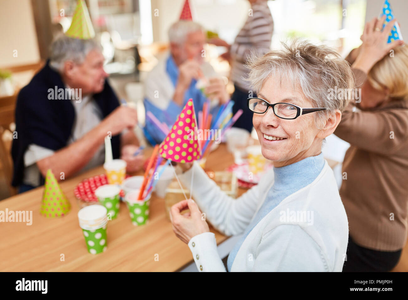 Old woman and seniors friends celebrate birthday party together at retirement home - Stock Image
