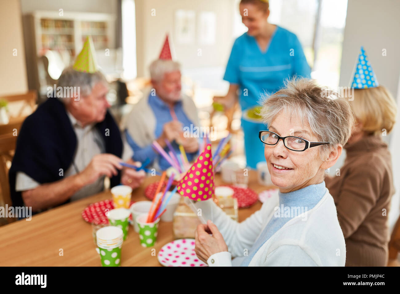 Happy seniors at a birthday party in retirement home at the coffee table - Stock Image