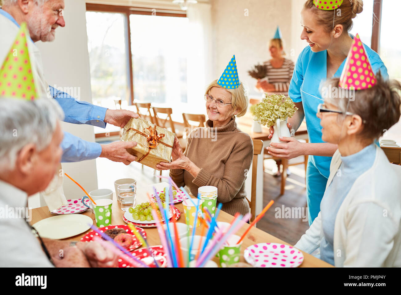 Senior woman receives a present presented at her birthday party at the retirement home - Stock Image