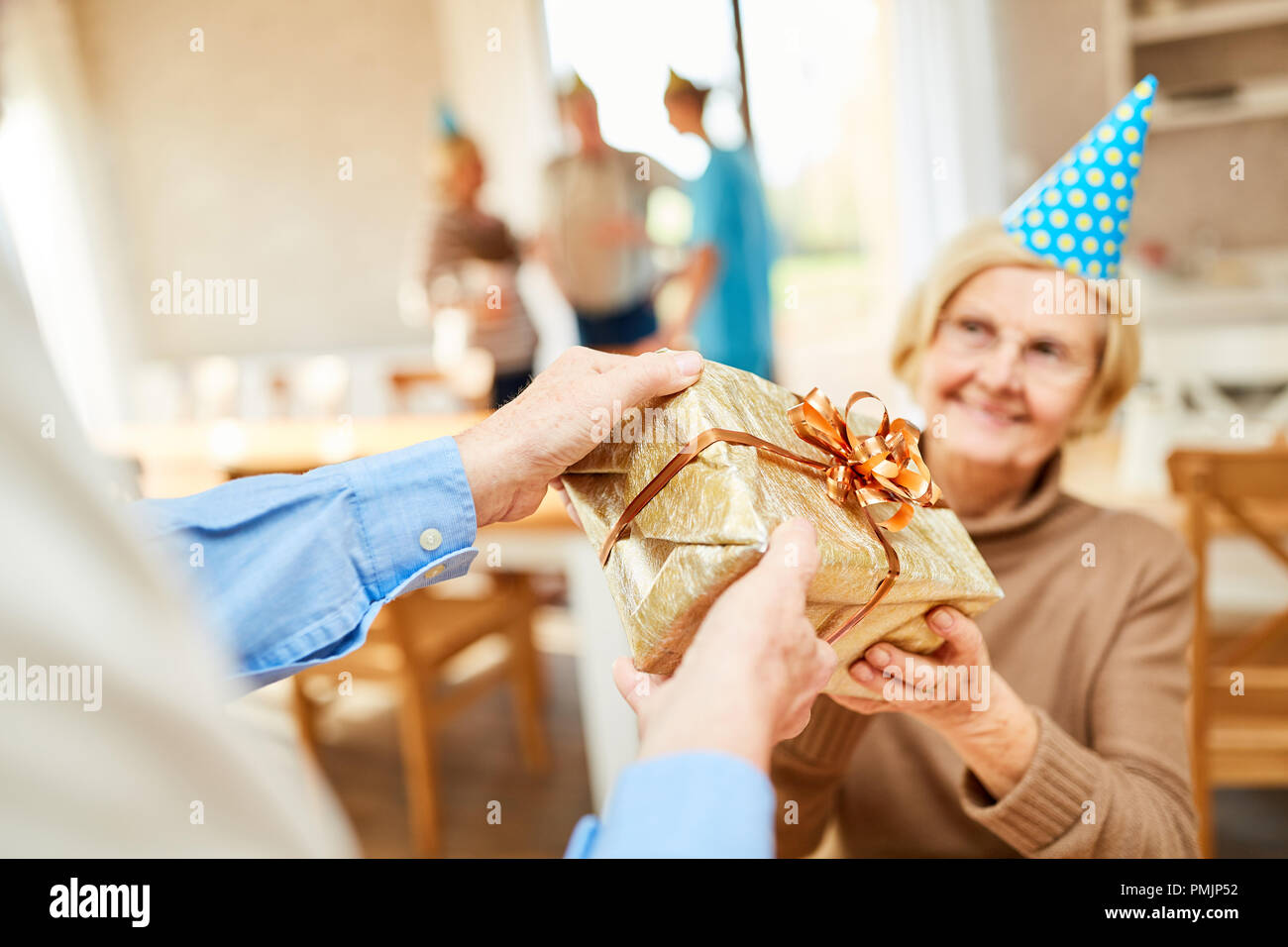 Senior woman is surprised with a gift at her birthday party in retirement home - Stock Image