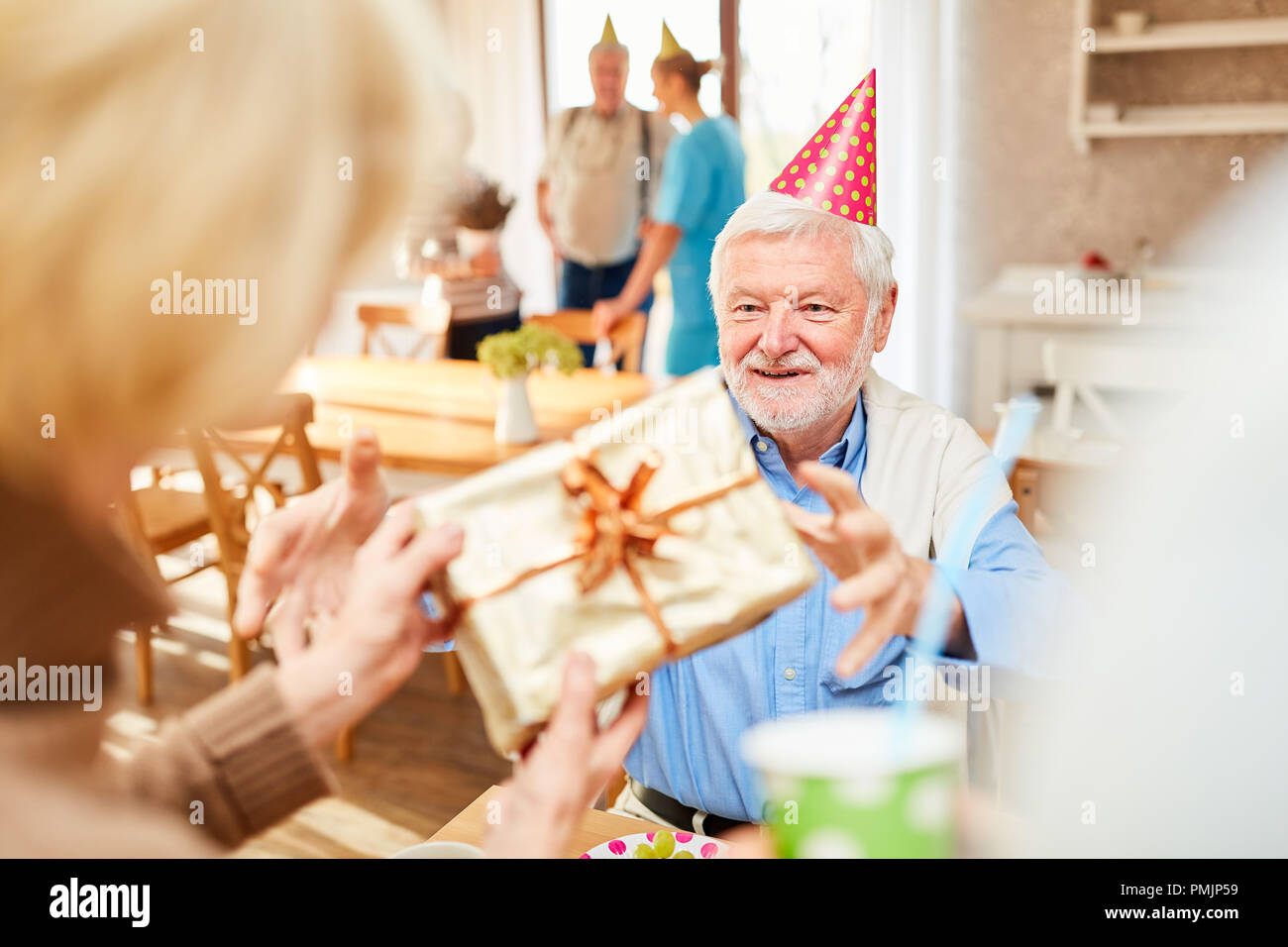 Senior man smiles happily over a gift for his birthday at the retirement home - Stock Image