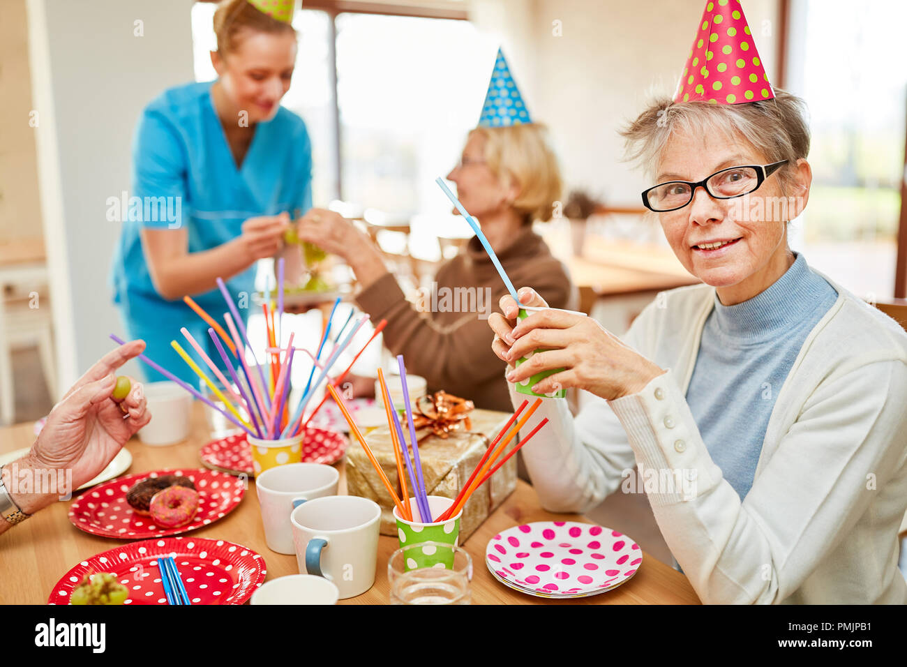 Seniors sit together and drink coffee at a birthday party in the retirement home - Stock Image
