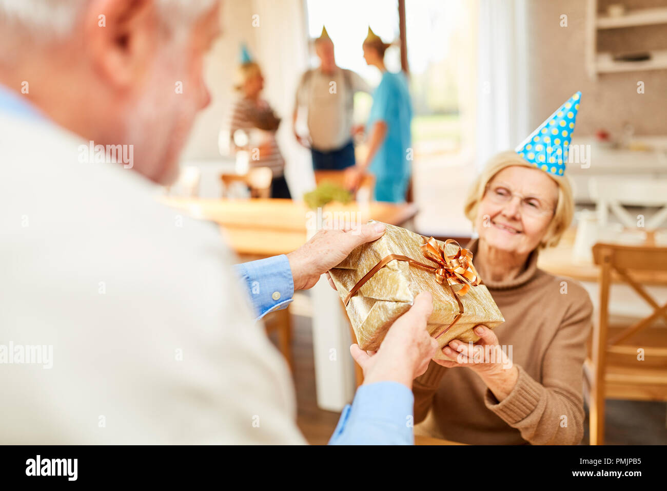 Senior gets a birthday present at her birthday party at the retirement home - Stock Image
