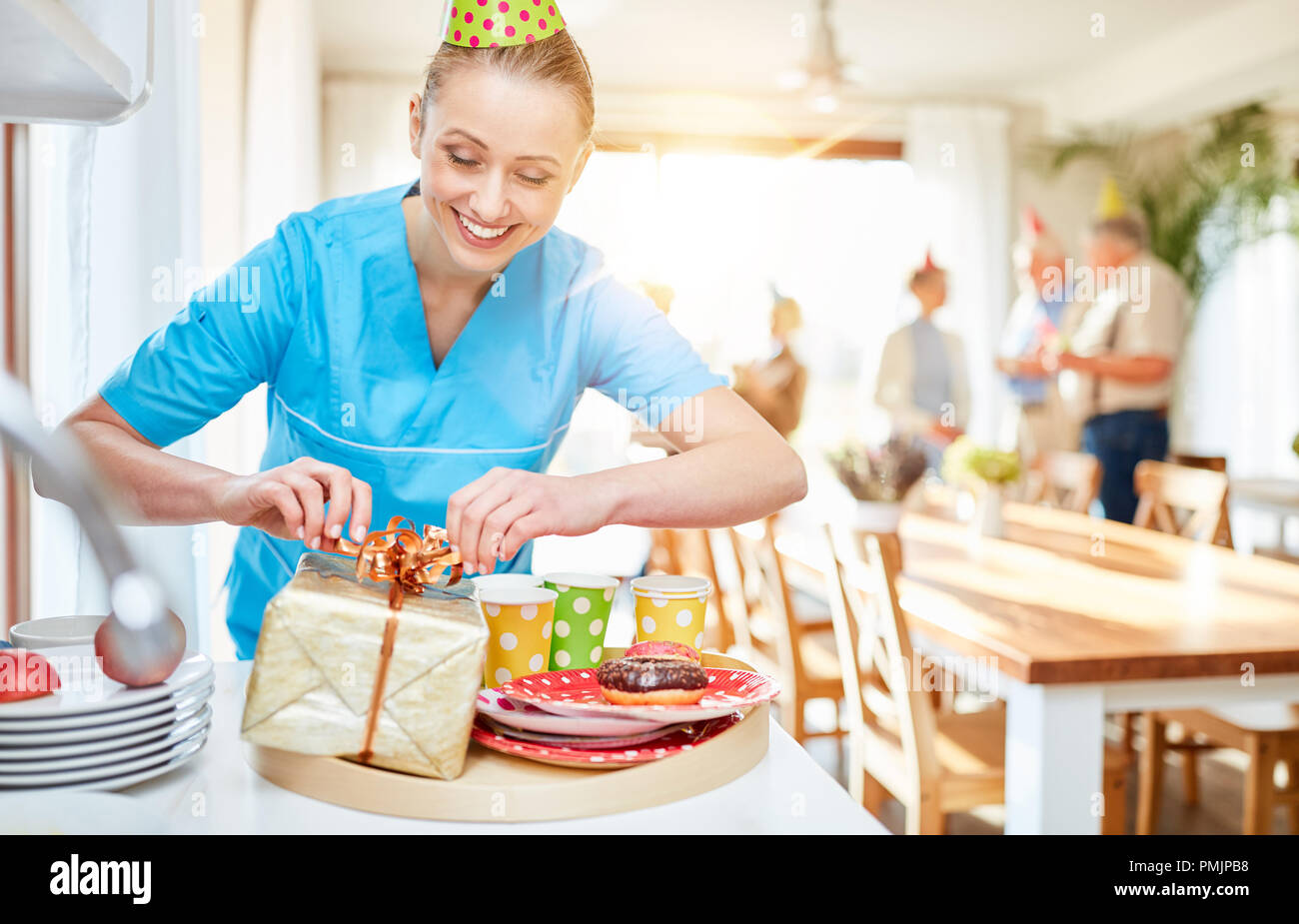 Caregiver packs gift for seniors in retirement home before a birthday party - Stock Image