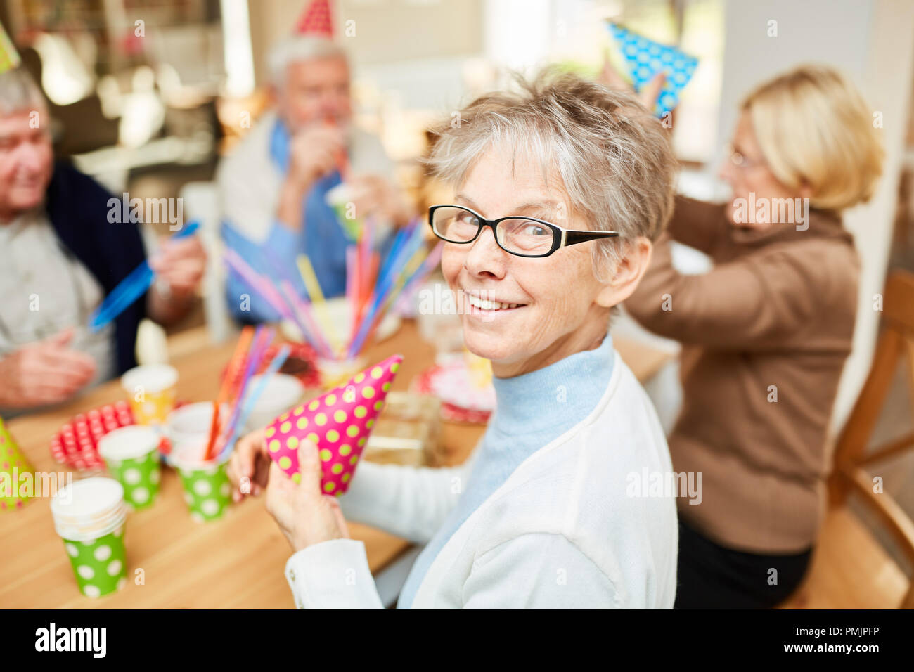 Senior woman in retirement home celebrates carnival or birthday together with friends - Stock Image