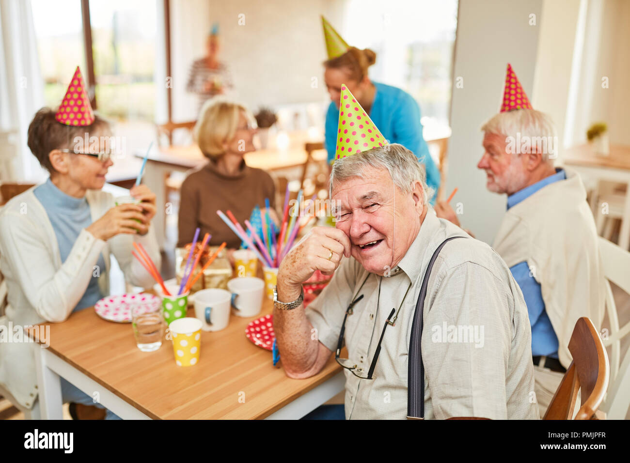 Seniors celebrate birthday together in a retirement home and have fun together - Stock Image