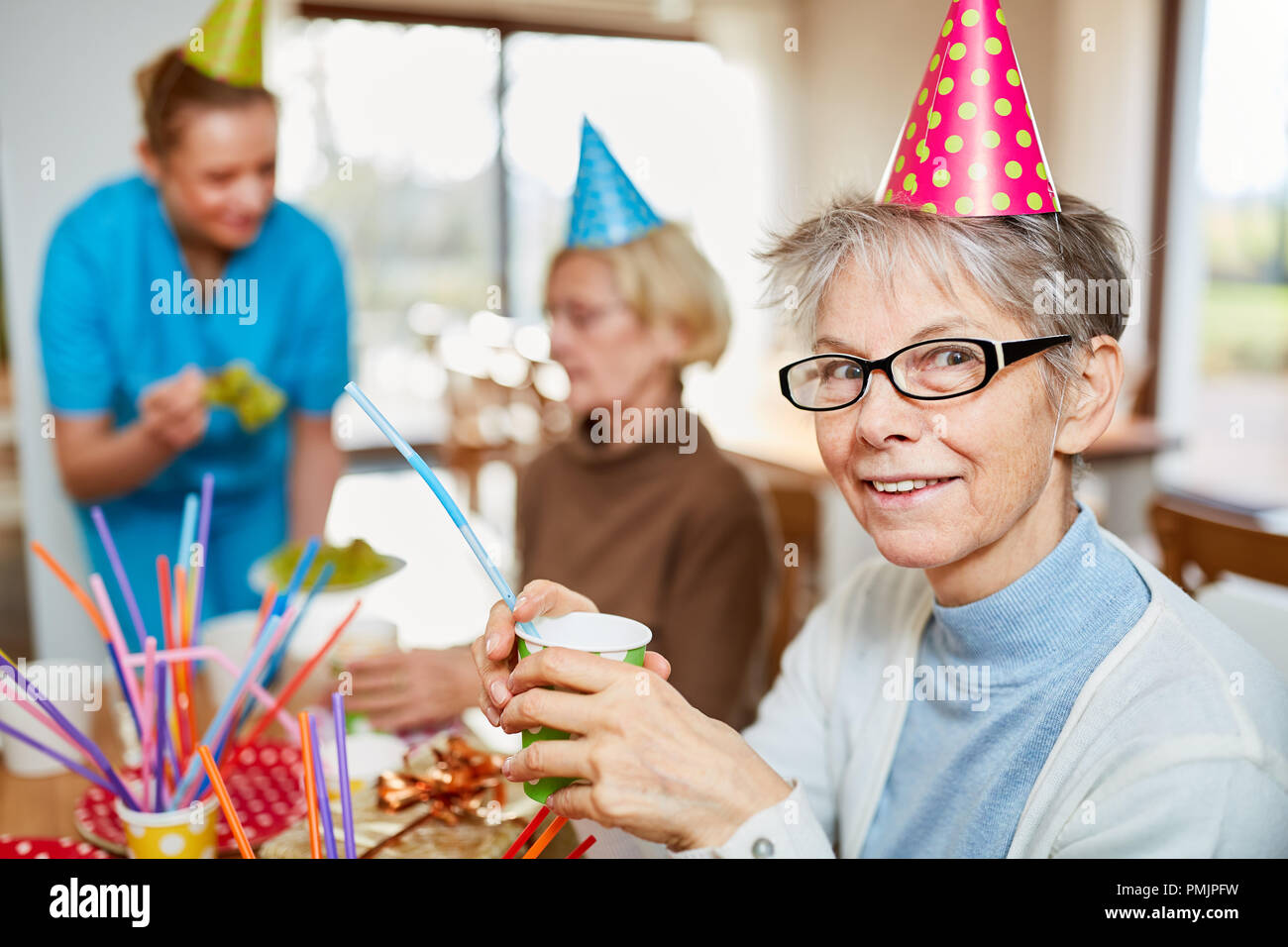 Senior woman in retirement home celebrates carnival together with friends and family - Stock Image