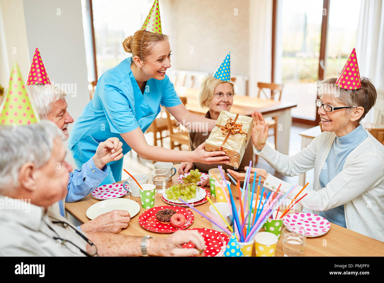 Caregiver hands over a gift package to an old woman at her birthday party - Stock Image