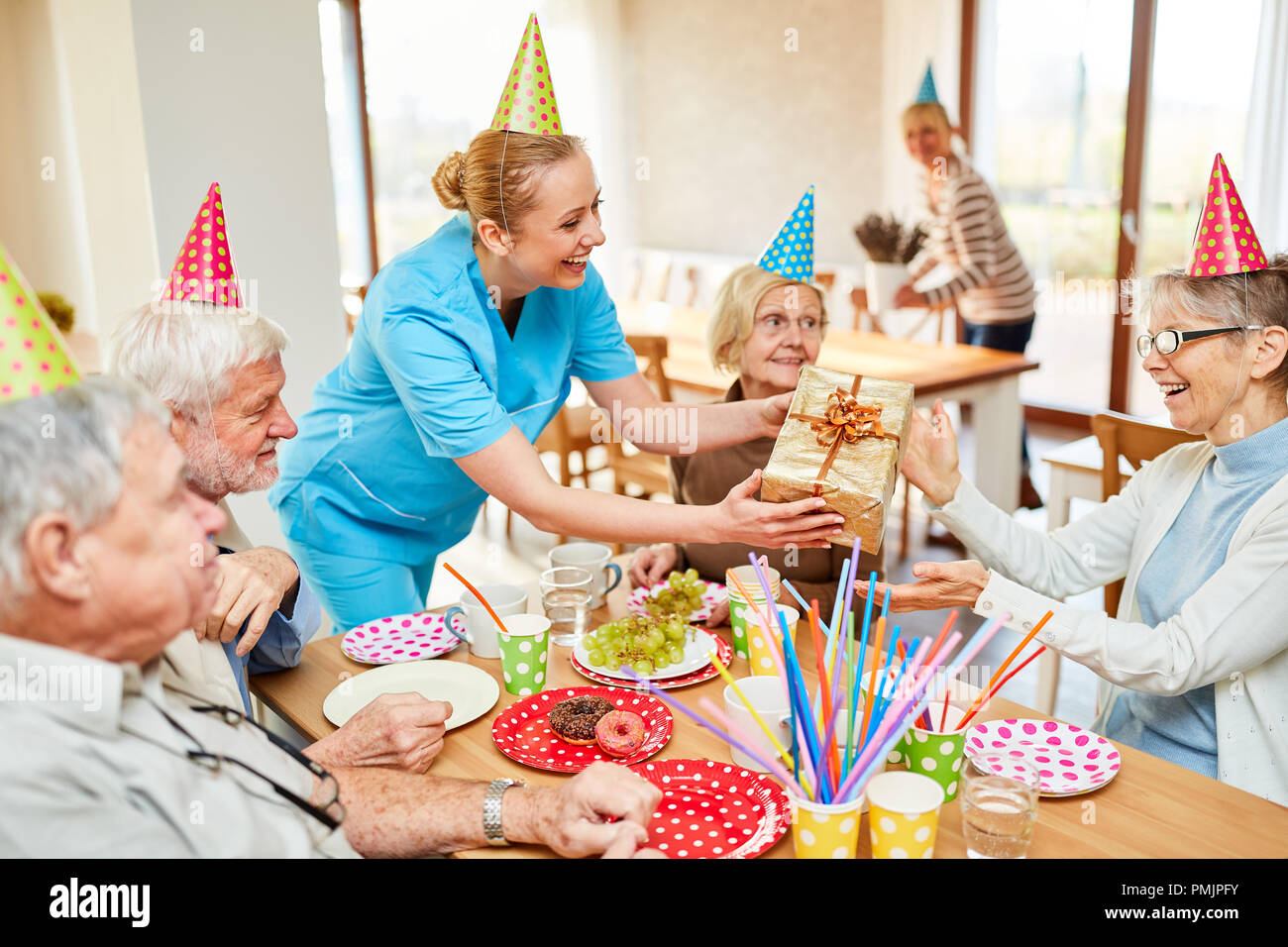 Nursing help gives a birthday present to a senior citizen at the coffee table in the retirement home - Stock Image