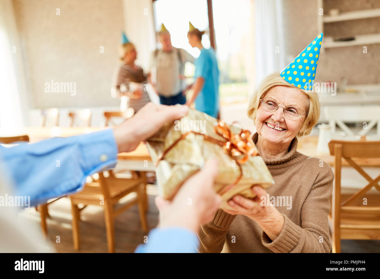 A senior as a birthday child is happy about a present at her birthday party - Stock Image