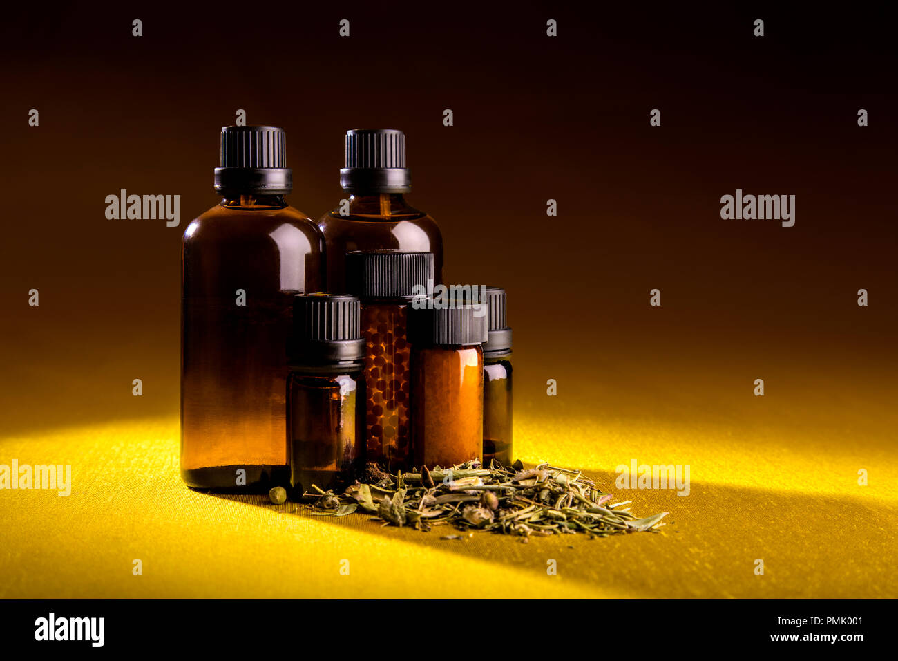Studio shot of glass bottles of homeopathic tinctures, pills and herbs scattered Stock Photo