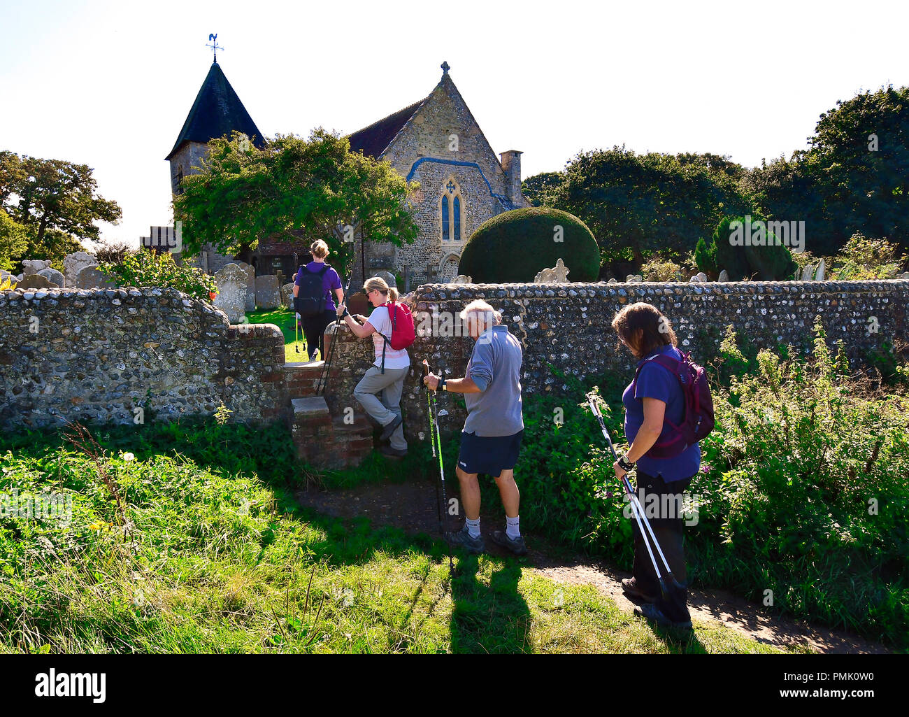Walkers on public foot path at Snow Hill crossing  the stile in the flint wall over to st peter and paul church West Wittering, West Sussex, UK Stock Photo