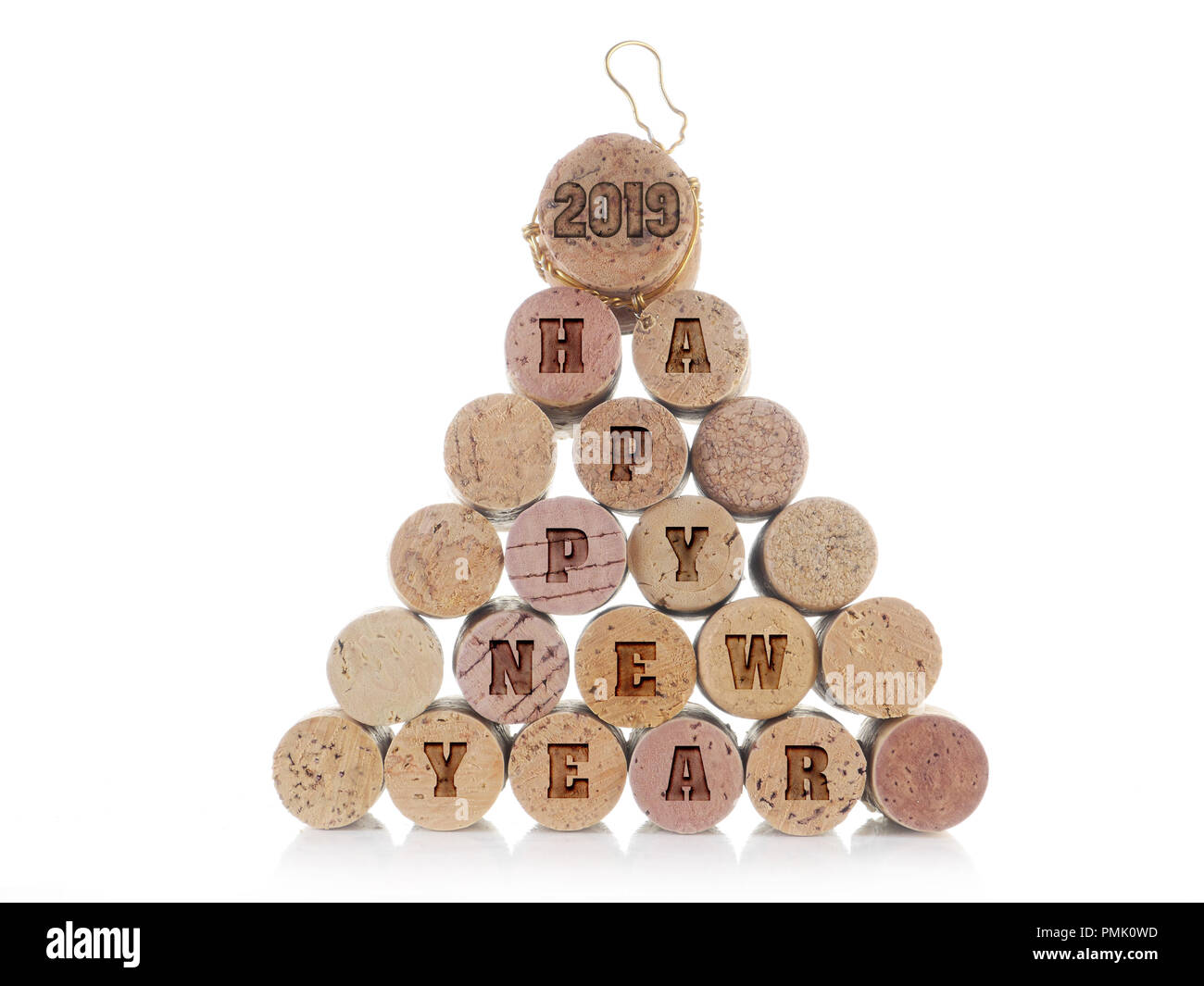 wine and champagne corks arranged into pyramid with imprinted 2019 happy new year words over white background