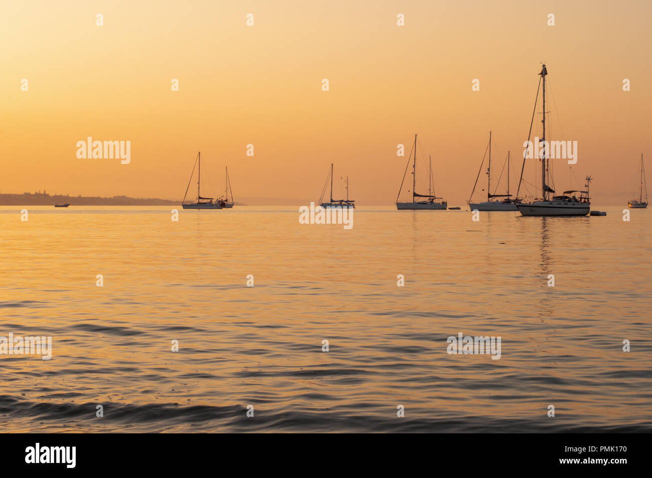 Sunrise with Sailing Yachts Anchored at Sea - Stock Image