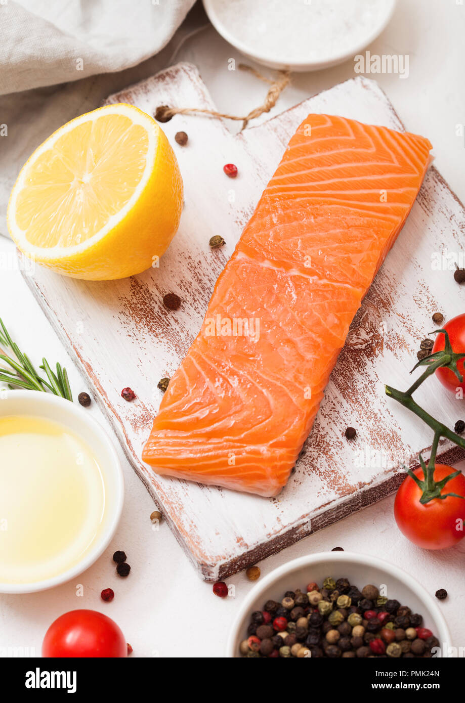 Plastic container with fresh salmon slice with oil tomatoes and