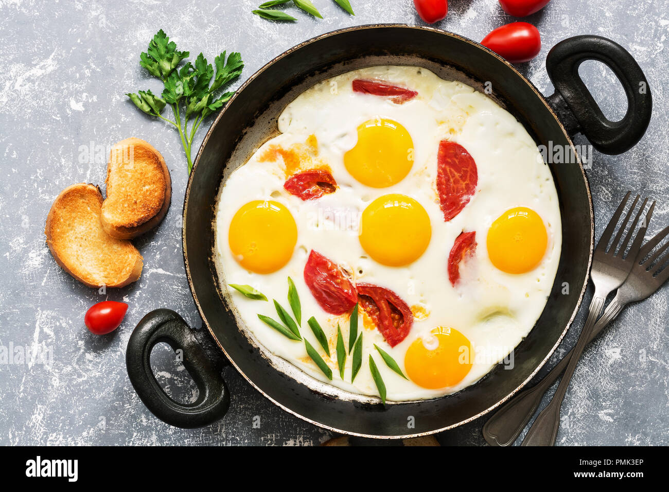 Fried eggs with tomatoes in a frying pan, gray background.Flat lay. - Stock Image