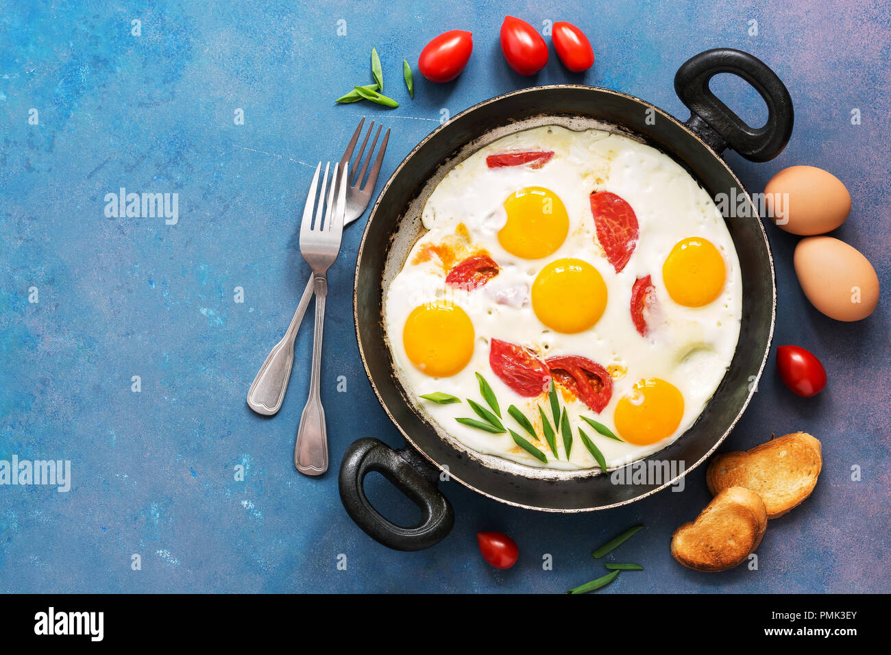 Breakfast fried eggs with tomatoes, served in a pan on a blue background. Top view, space for text - Stock Image