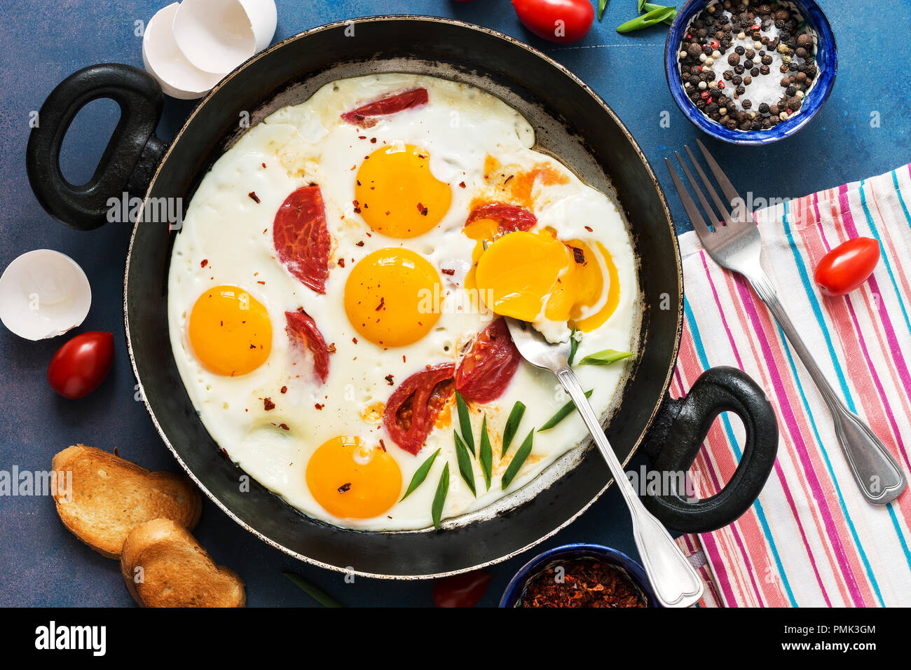 Fried eggs with cherry tomatoes in a pan. Fresh and hearty Breakfast. The view from the top - Stock Image