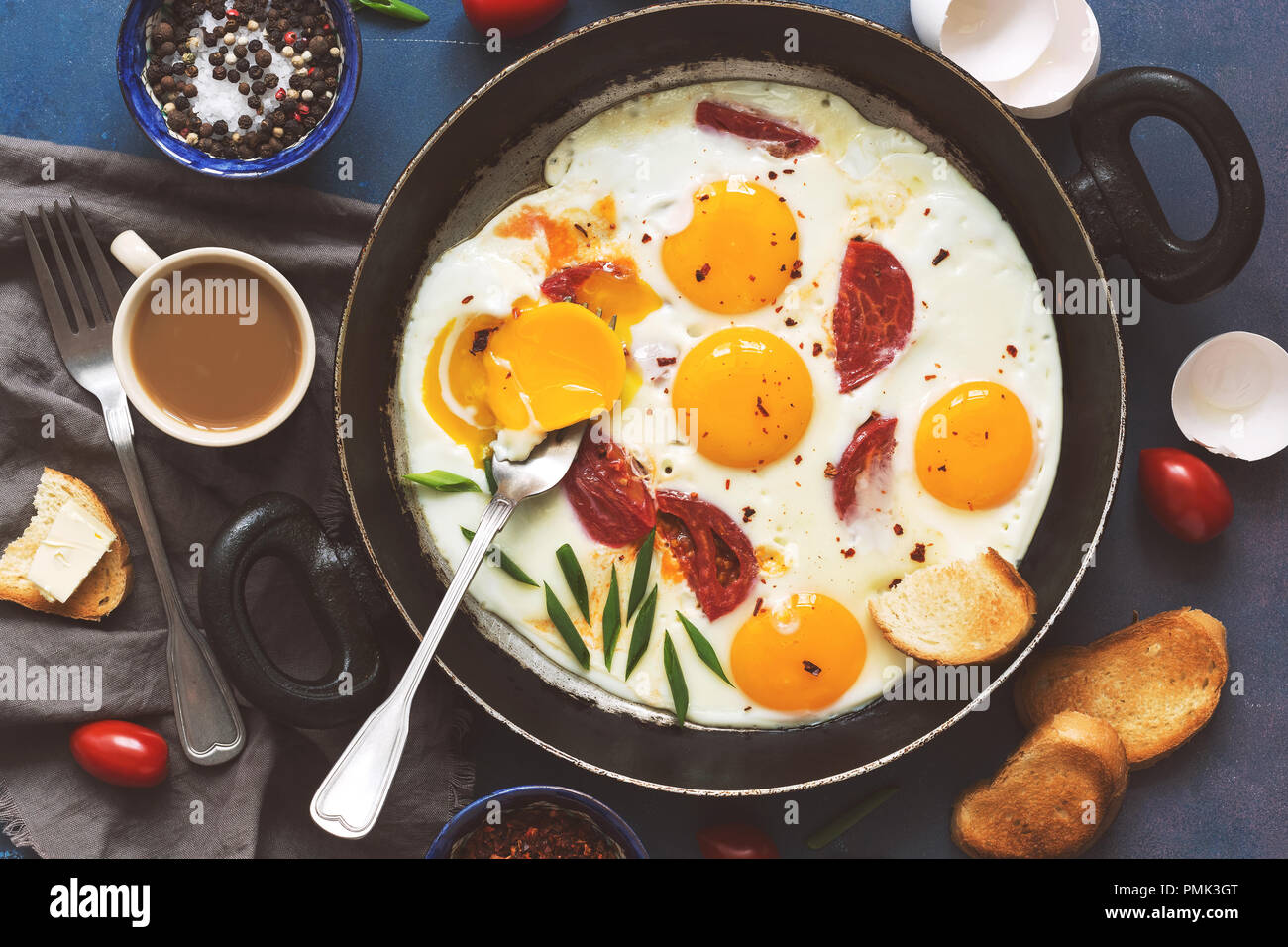 Flat lay fried eggs with tomatoes in a pan, toast with butter, coffee. A hearty Breakfast on a blue background - Stock Image