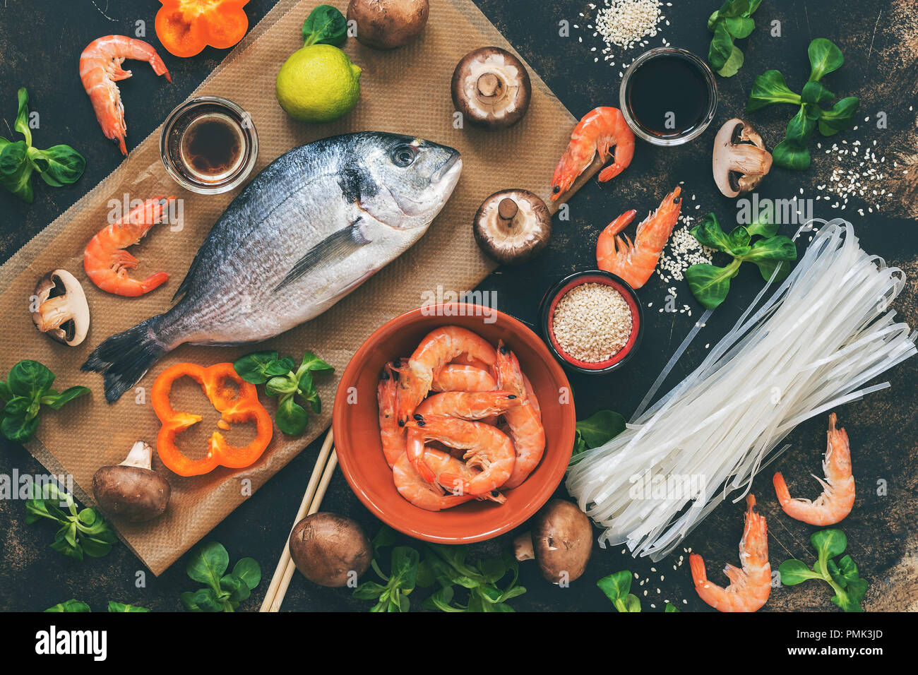 Ingredients for Asian dishes - raw Dorado fish, shrimp, rice noodles,mushrooms, vegetables, dark background, top view. Flat lay, toned photo - Stock Image