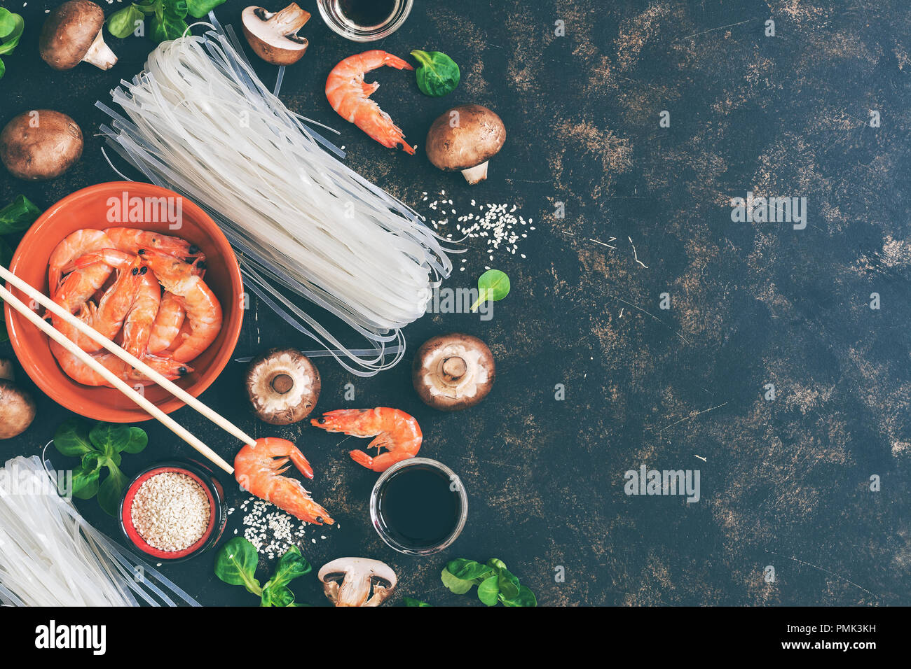 Background with Asian ingredients - rice noodles, shrimps, mushrooms, sesame, salad corn, dark background. Flat lay,copy space. toned photo - Stock Image