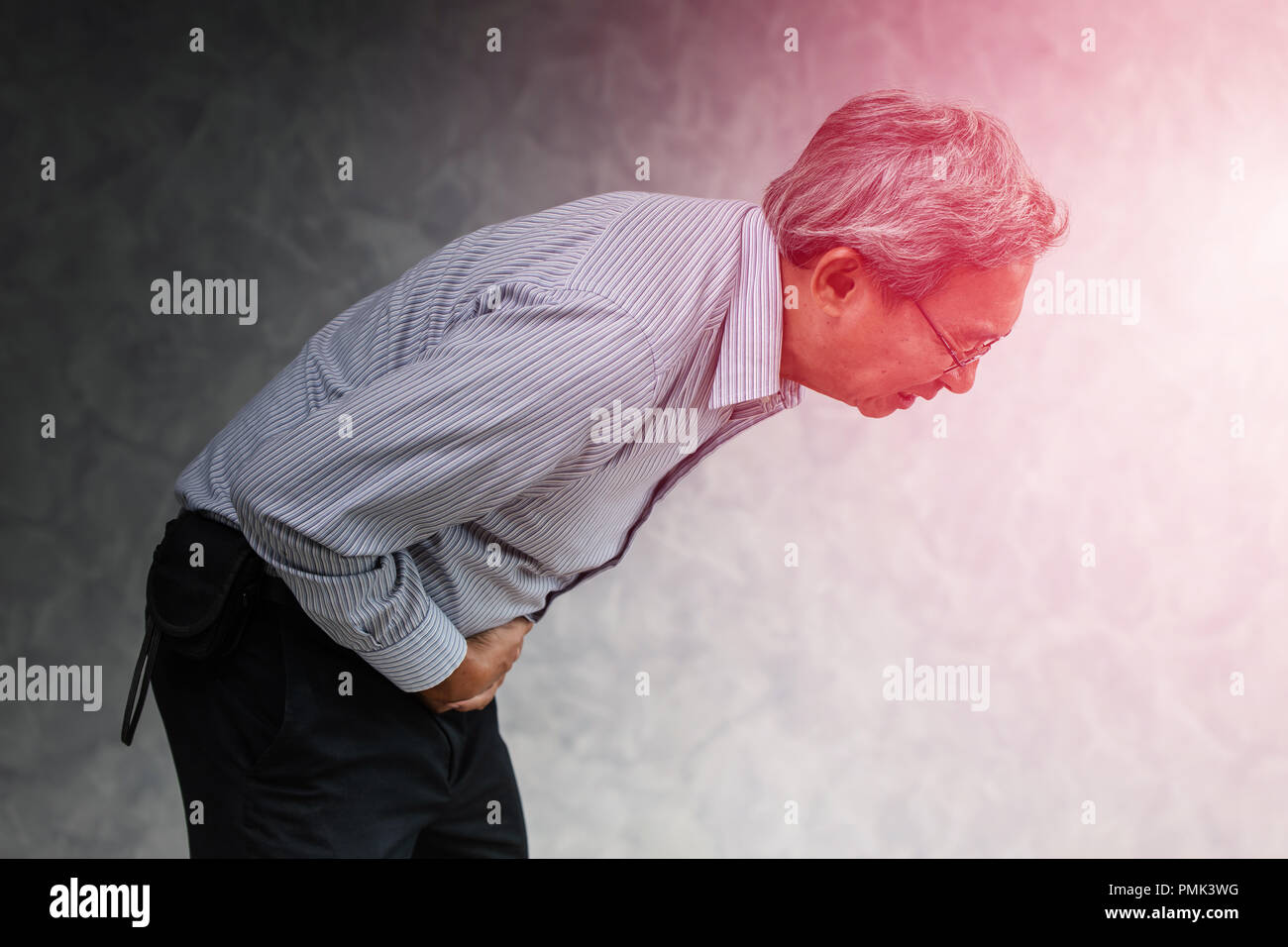 Asian senior office male suffering pain from stomach ache diarrhea expression. - Stock Image
