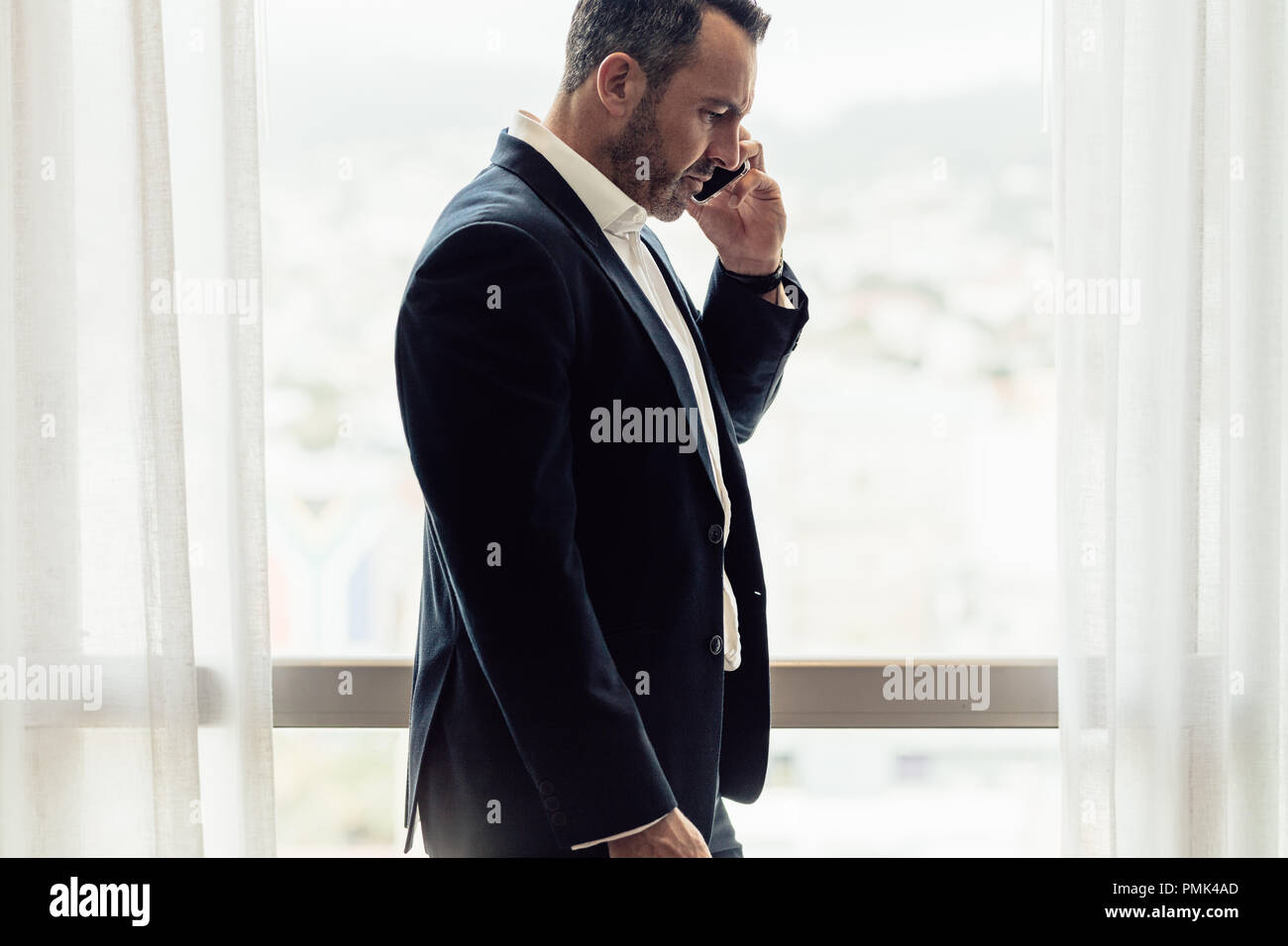 Side view of mature businessman talking on cell phone. Man in hotel room having discussing over phone. - Stock Image
