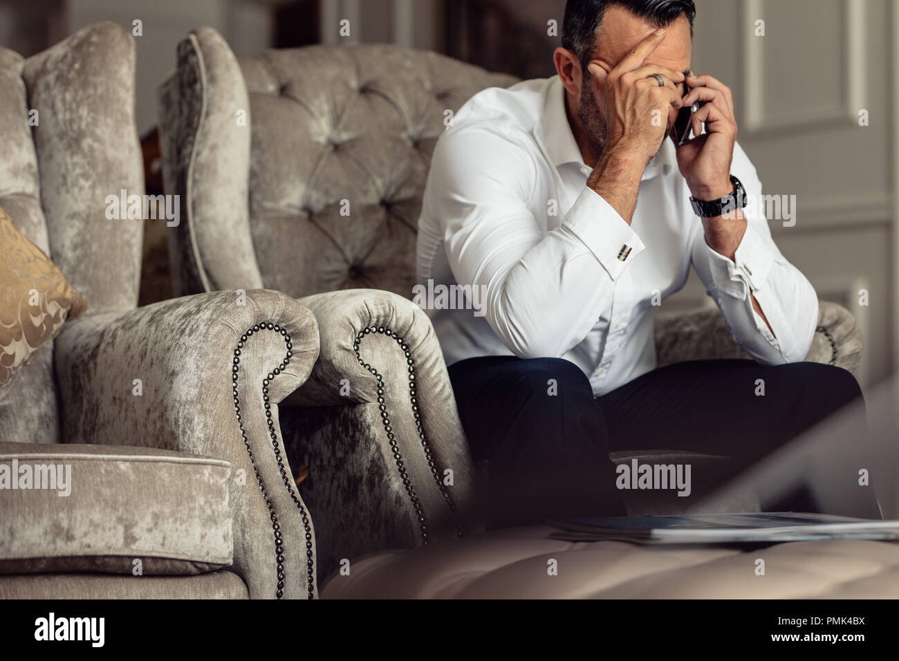Portrait of stressed mature businessman sitting in a hotel room and talking on phone. Businessman sitting on couch with hand on head talking on cell p - Stock Image