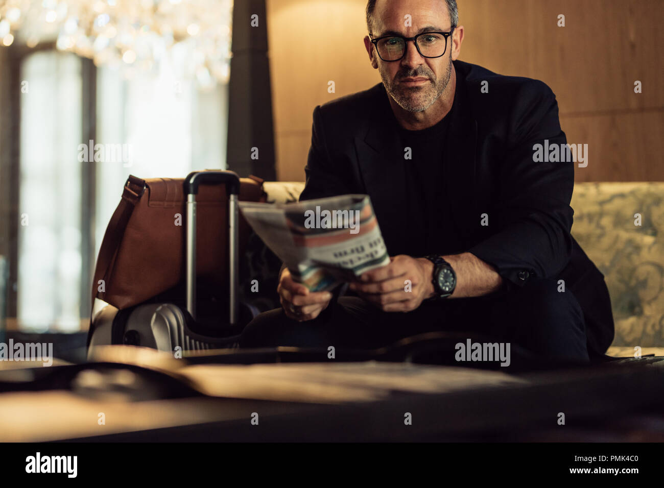 Portrait of confident mature businessman sitting in hotel foyer with his luggage on the side. CEO waiting in hotel lobby. - Stock Image