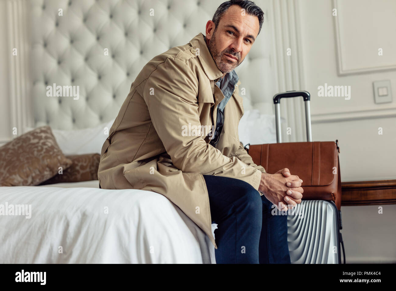 Traveling for work. Handsome mature businessman sitting in his hotel room bed and looking at camera. - Stock Image
