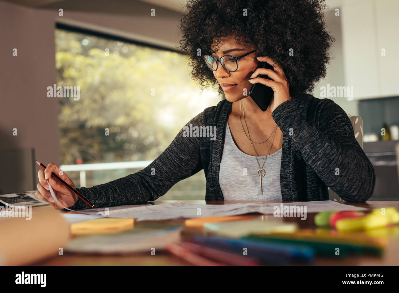 Businesswoman talking on smartphone and working in office. African female architect sitting at his workplace at home. - Stock Image