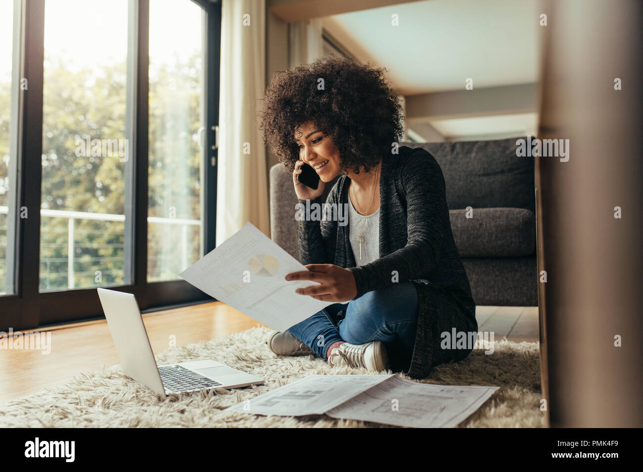 Smiling young woman sitting on floor with few reports talking on cell phone. African female working from home. - Stock Image