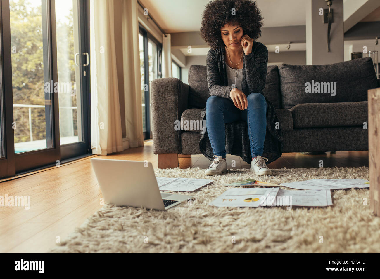 Woman sitting on sofa looking at the papers lying on floor with a laptop. Woman working on a project from home. - Stock Image