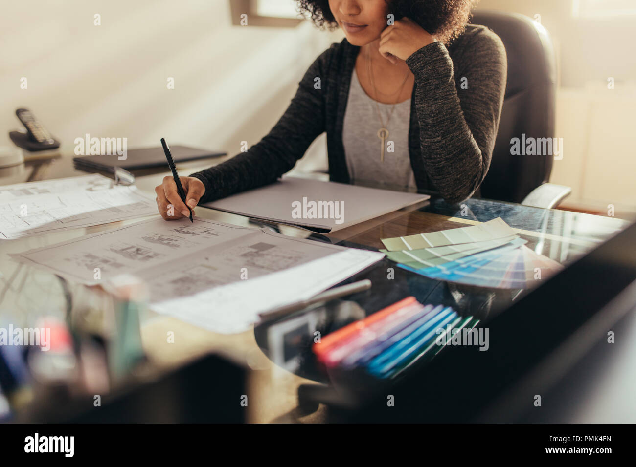 Female architect working on house floor designs at her work desk. Woman preparing new building plan while sitting at her work desk. - Stock Image