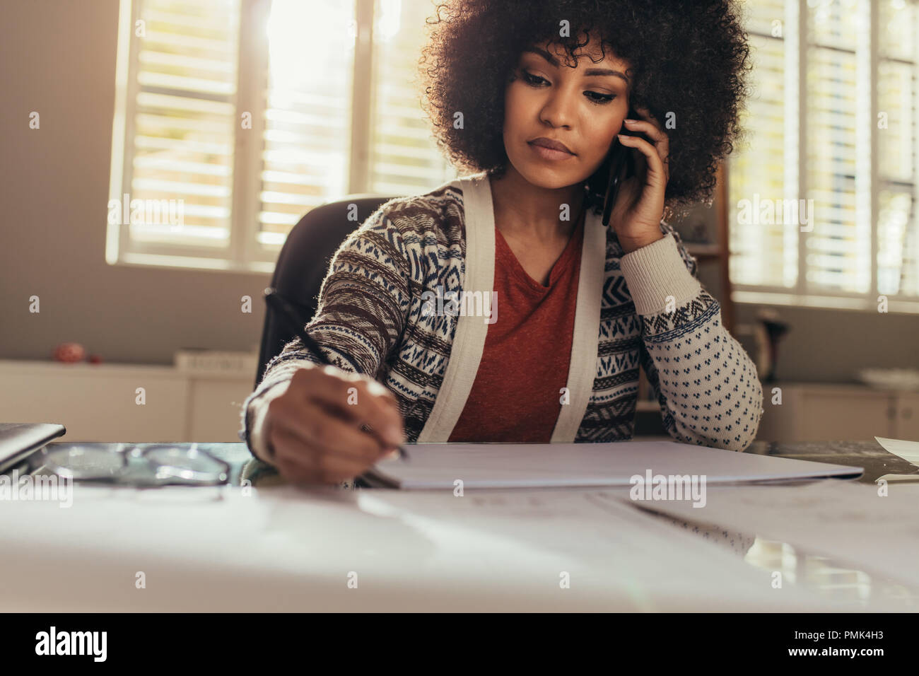 Female architect talking on phone while making new drawing for housing project. Woman making new building plan and talking on mobile phone while sitti Stock Photo