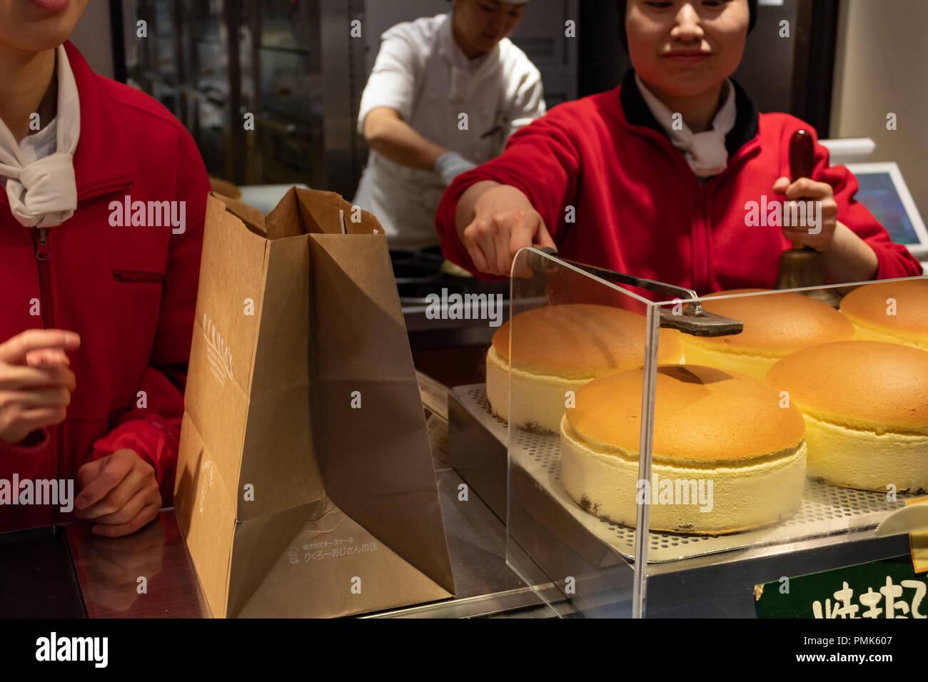 OSAKA, JAPAN - JAN 29, 2018: Woman marking with fire the famous japanese sponge cake in Rikuro Ojisan store - Stock Image