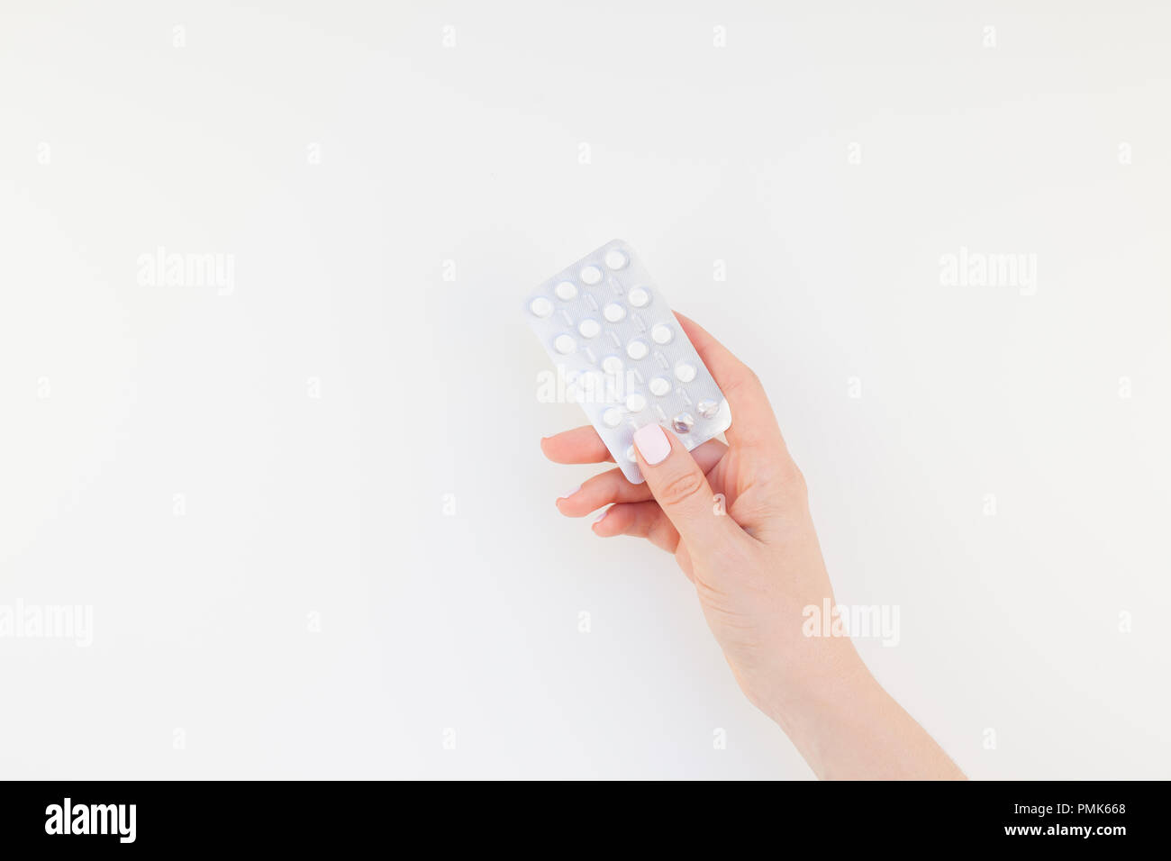 woman hand with pastel manicure polish holding pills in blister