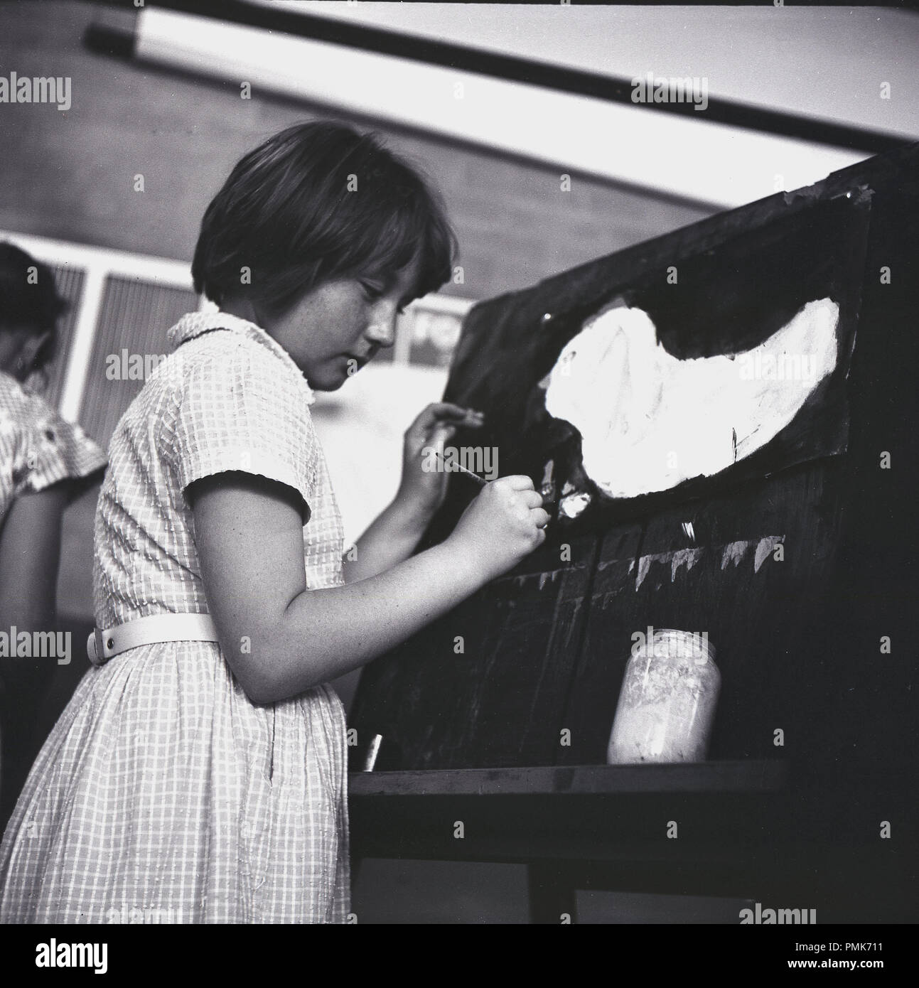 1960s, young schoolgirl in a clasroom standing by an easel painting a picture, a watercolour, England, UK. - Stock Image