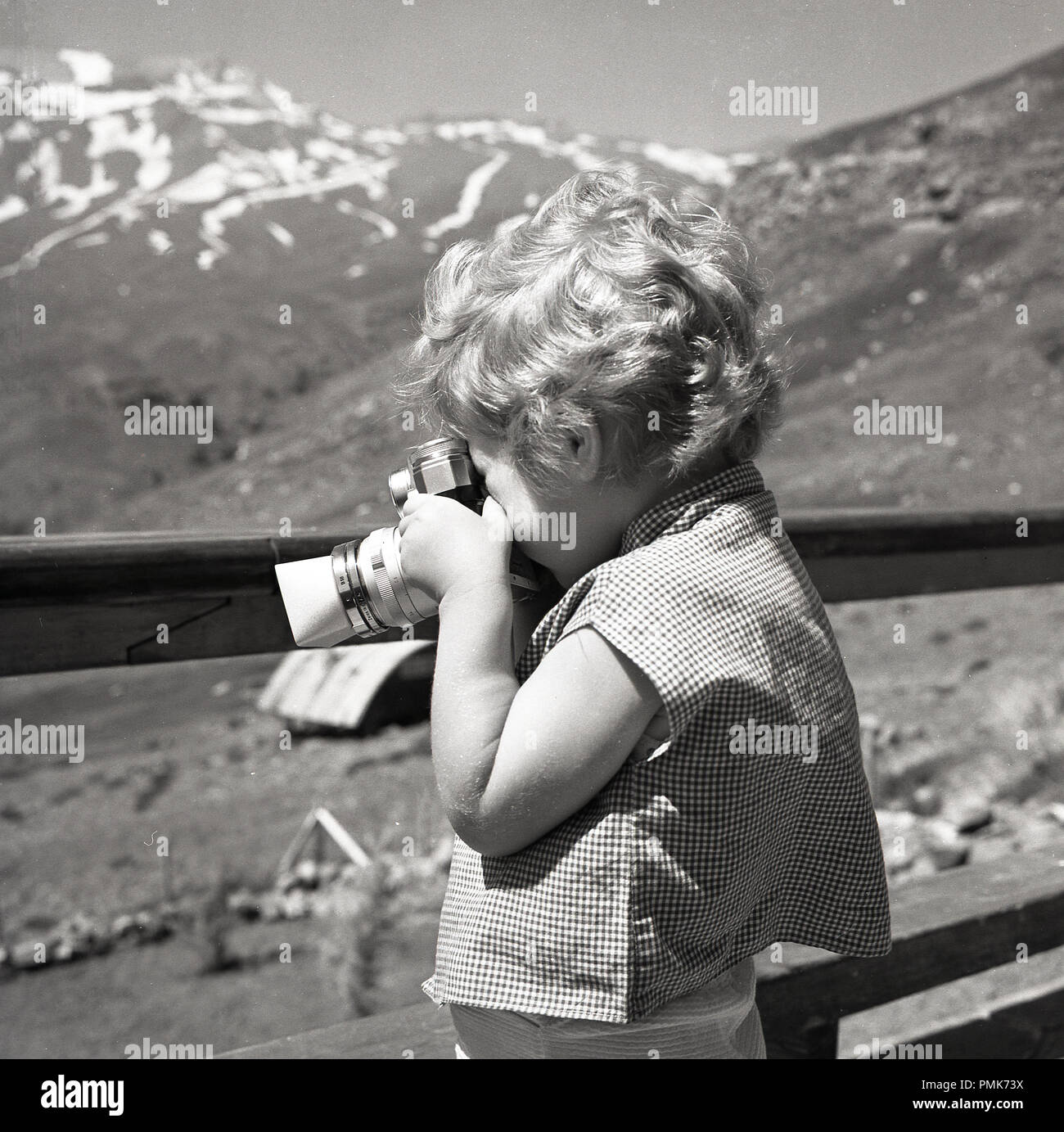 1960s, a bright, sunny day in the mountains and a young child holding a 35mm film camera to take a photograph. Notice the lens hood attached to the camera, used to prevent glare and block the sun's rays. - Stock Image