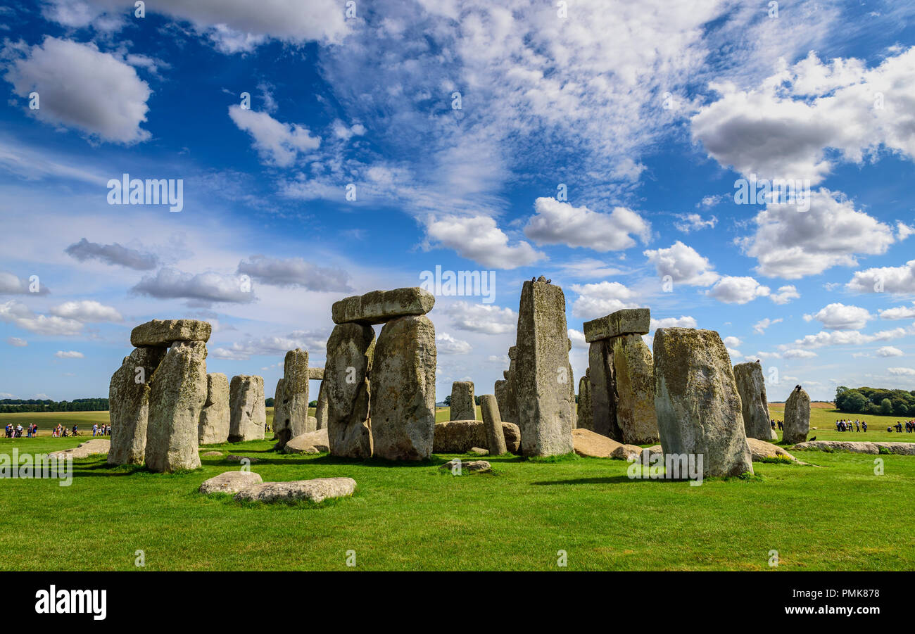 Stonehenge, against a bright blue sky with light clouds - Stock Image