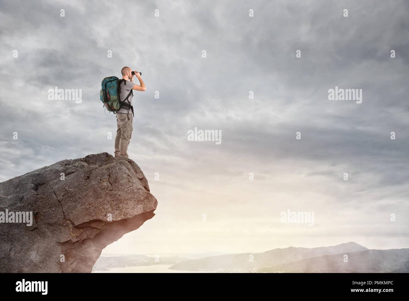 Explorer on the peak of a mountain - Stock Image