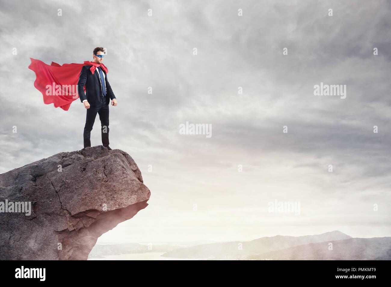 Businessman as a super hero on the peak of a mountain - Stock Image