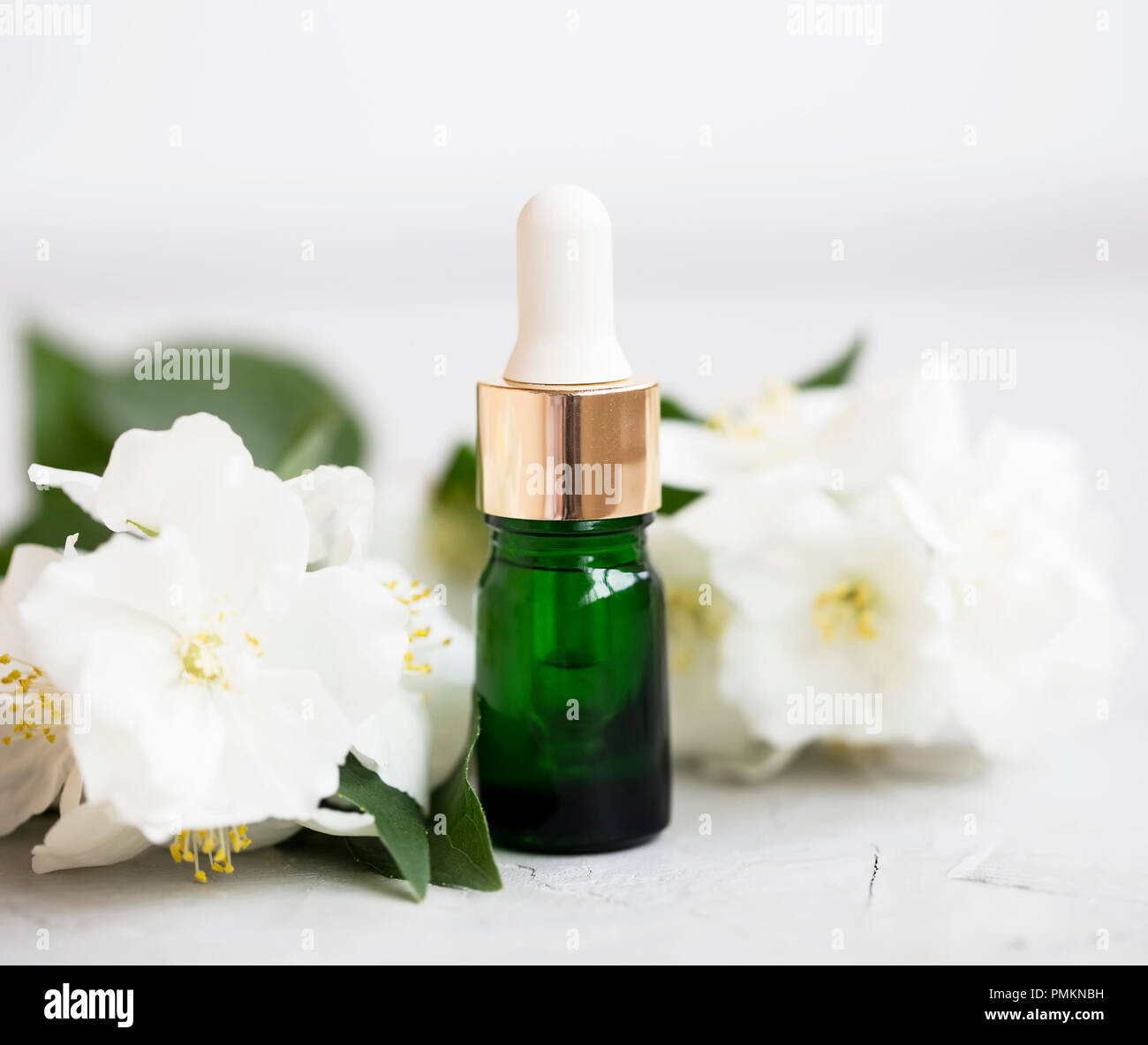 Jasmine oil bottle with flowers, natural aromatherapy oil Stock