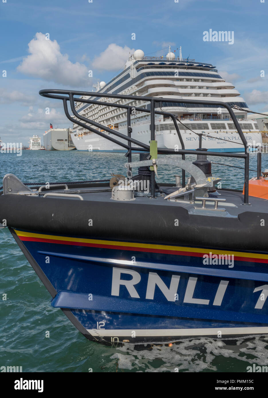 an RNLI lifeboat with the navigator  of the seas massive cruise liner in the background. - Stock Image