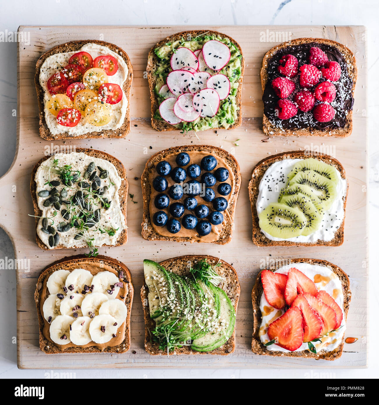 Slices of toast with a variety of healthy toppings - Stock Image